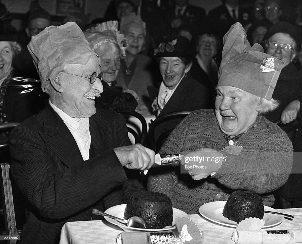 The two oldest members of the Laindon Darby and Joan Club pull a cracker during the club's Christmas party at the Memorial Hall, Laindon, Essex.