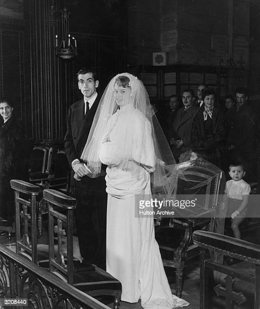 Fulllength portrait of French actor Brigitte Bardot and her husband French director Roger Vadim standing at the altar during their wedding ceremony...