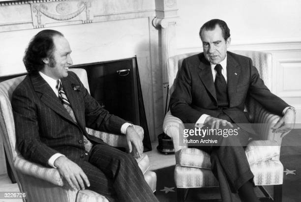 US president Richard Nixon consults Canadian Prime Minister Pierre Trudeau on Nixon's trip to Communist China while sitting in armchairs at the White...