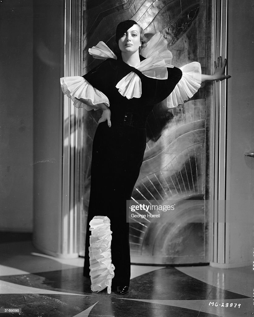 American actress Joan Crawford wearing a black and white evening dress with frills around the collar cuffs and hem