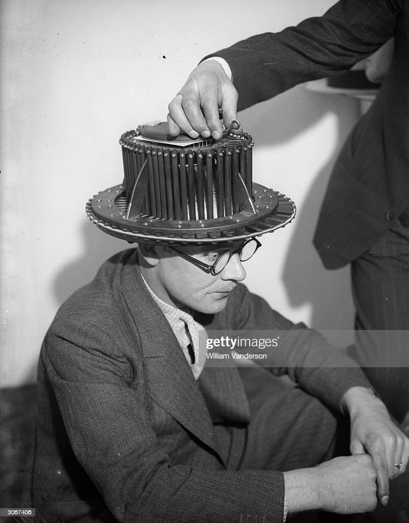 A man wearing a scalpograph, which traces the outline of the head to ensure a well fitting hat, at the menswear exhibition at Dorland Hall, London.