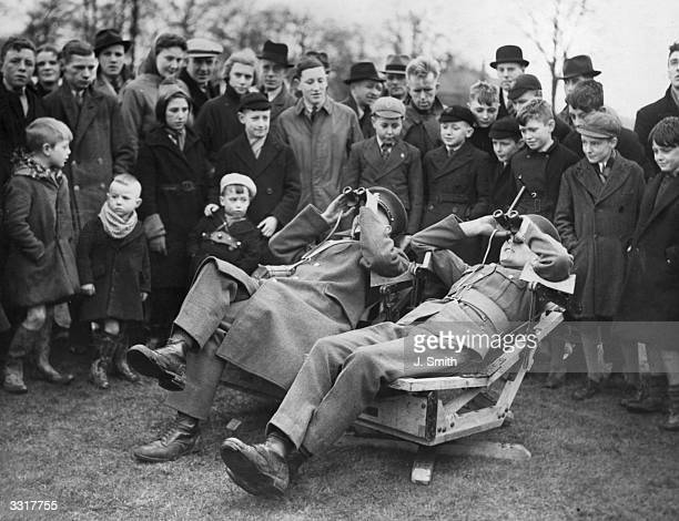 A crowd watching soldiers reclining in 'spotting chairs' at a public demonstration at Timperley Cricket Ground Timperley Cheshire The soldiers are...