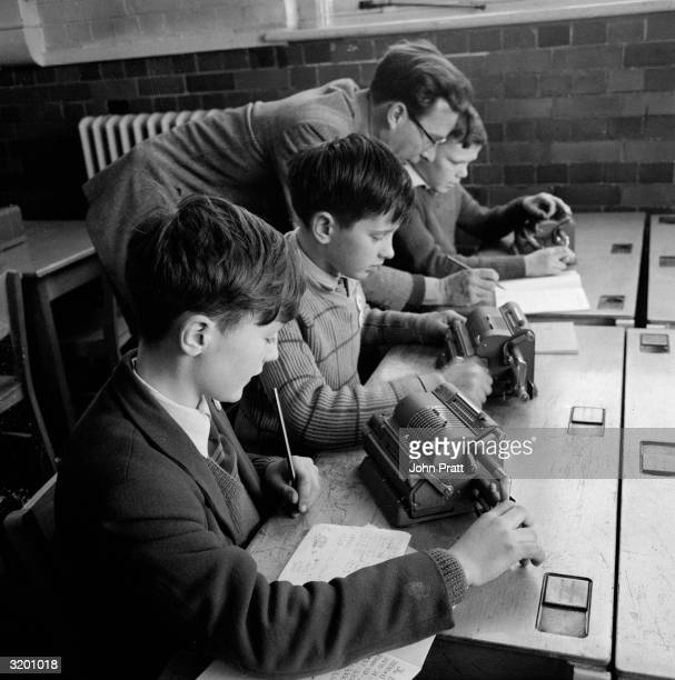 Headmaster Peter Finch helps pupils John Morse Adrian Pride and Timothy Fry to use mechanical adding machines or 'computers' in a maths lesson at...