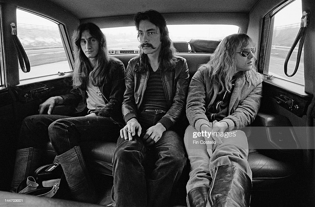 Canadian progressive rock band Rush posed sitting in a car in Birmingham England during their 'Farewell To Kings' tour on 12th February 1978 Left to...