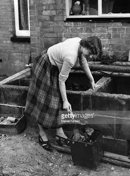 A housewife filling a bucket with coal from the coal bunker Original Publication Picture Post 5648 Fuel pub 1952