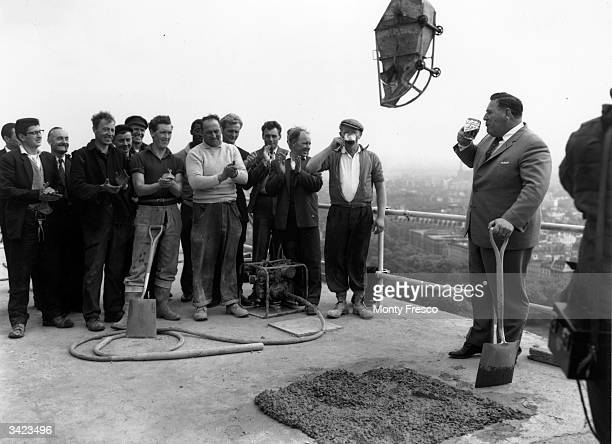 At a 'topping off ceremony' L T Mottram of the Token Construction Company drinks a toast of beer to some of the men who have helped with the...