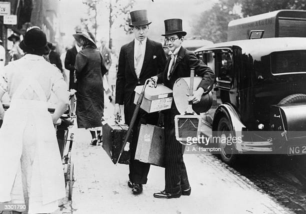 An Eton schoolboy arrives with his tennis racket and lunch basket at Lord's cricket ground for the school cricket match between Eton and Harrow