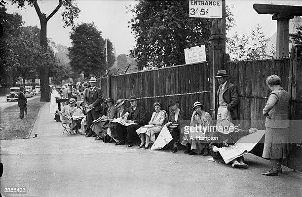 Tennis fans sitting on stools queuing outside the gates at Wimbledon London