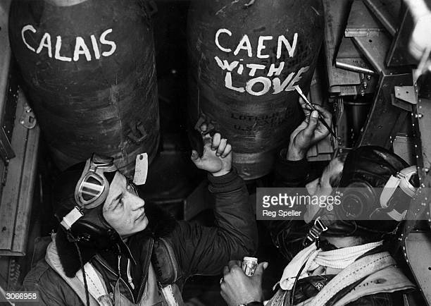 Airmen of the US 8th AAF paint slogans on their bombs before setting off for a raid over Caen and Calais