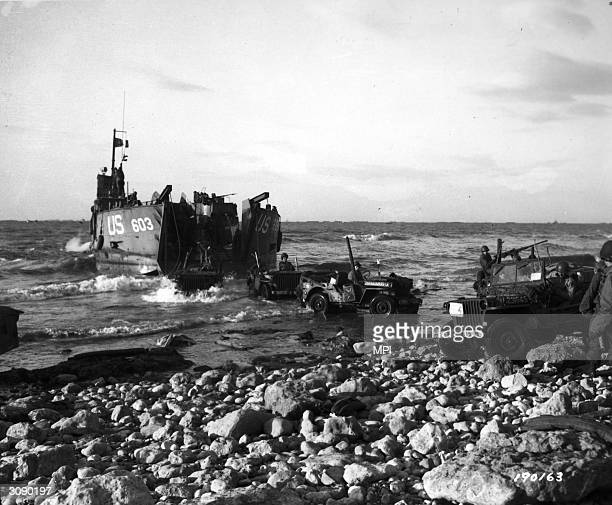 Jeeps of the 5th Engineer Special Brigade debark from a Landing Ship Tank at Fox Green Omaha Beach Normandy to aid the Army of Liberation on the...