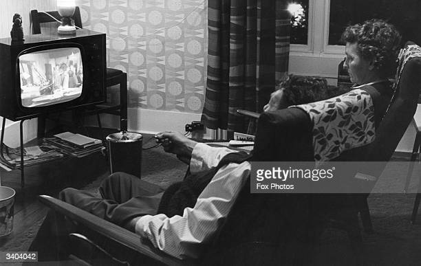 A couple watch the television in the comfort of their own home