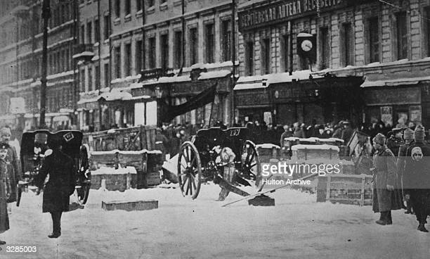 Barricades traversing a street in St Petersburg as a red flag floats above the cannons during the Russian Revolution