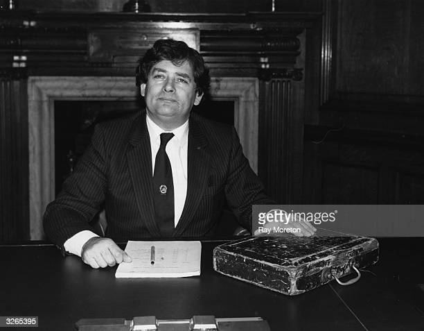 Chancellor of the Exchequer Nigel Lawson at his desk with red budget box