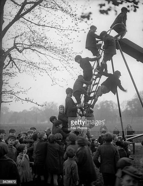 Boys queuing up to use a slide in the children's playground Regent's Park London
