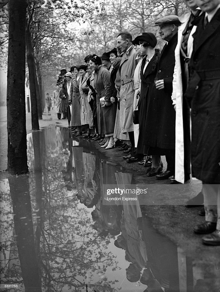Crowds line up to watch the coronation of King George VI on a wet day in London.