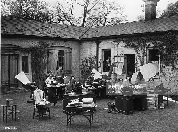 Typists at work in the garden of St Dunstans Headquarters in Regents Park London after a World War II bombing raid destroyed their office