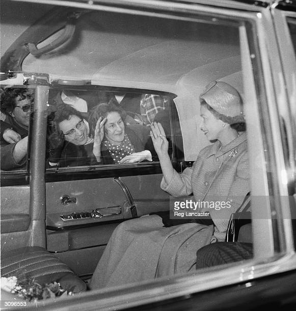 Queen Elizabeth II of Great Britain waving to crowds after visiting the King and Queen of Belgium at Ciergnon