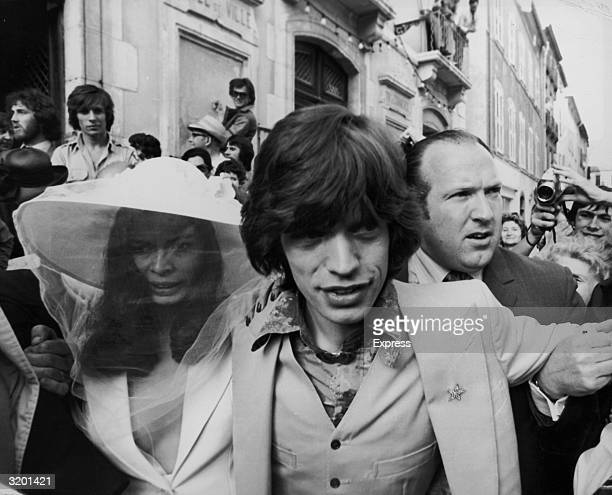 British rock singer Mick Jagger of the Rolling Stones and his new bride Bianca Perez Morena de Macias make their way through crowds on their wedding...