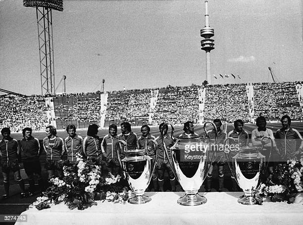 Winners for the third time the players of Bayern Munich football club stand in front of the three cups in the Munich Olympic stadium with the...