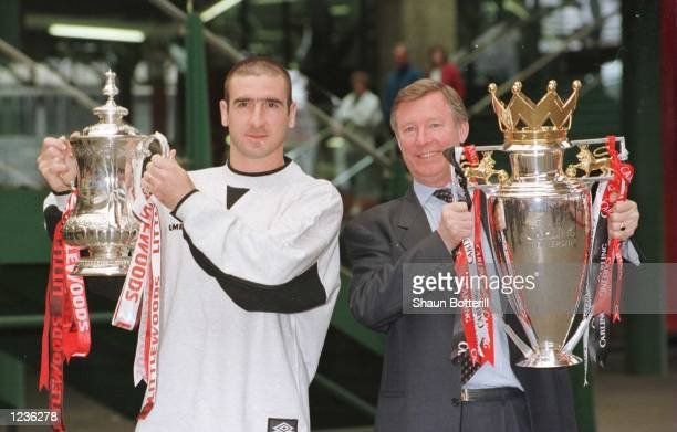 12th May 1996 Manchester United manager Alex Ferguson and Eric Cantona with the FA Cup and Premiership trophy on their arrival at Manchester's...