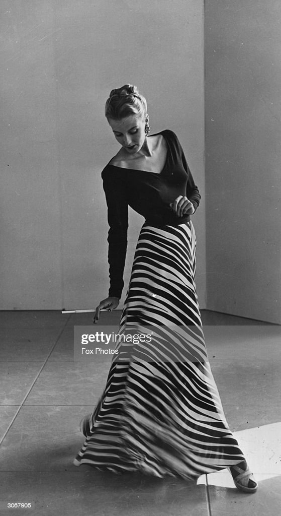 Holding a cigarette in a long holder Peggy Hunt models an evening dress with longsleeved vneck top and full length zebra print skirt
