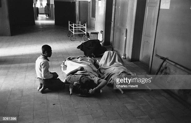 A boy watches over 2 wounded Gazans after the Israeli occupation Original Publication Picture Post 8738 pub 1956