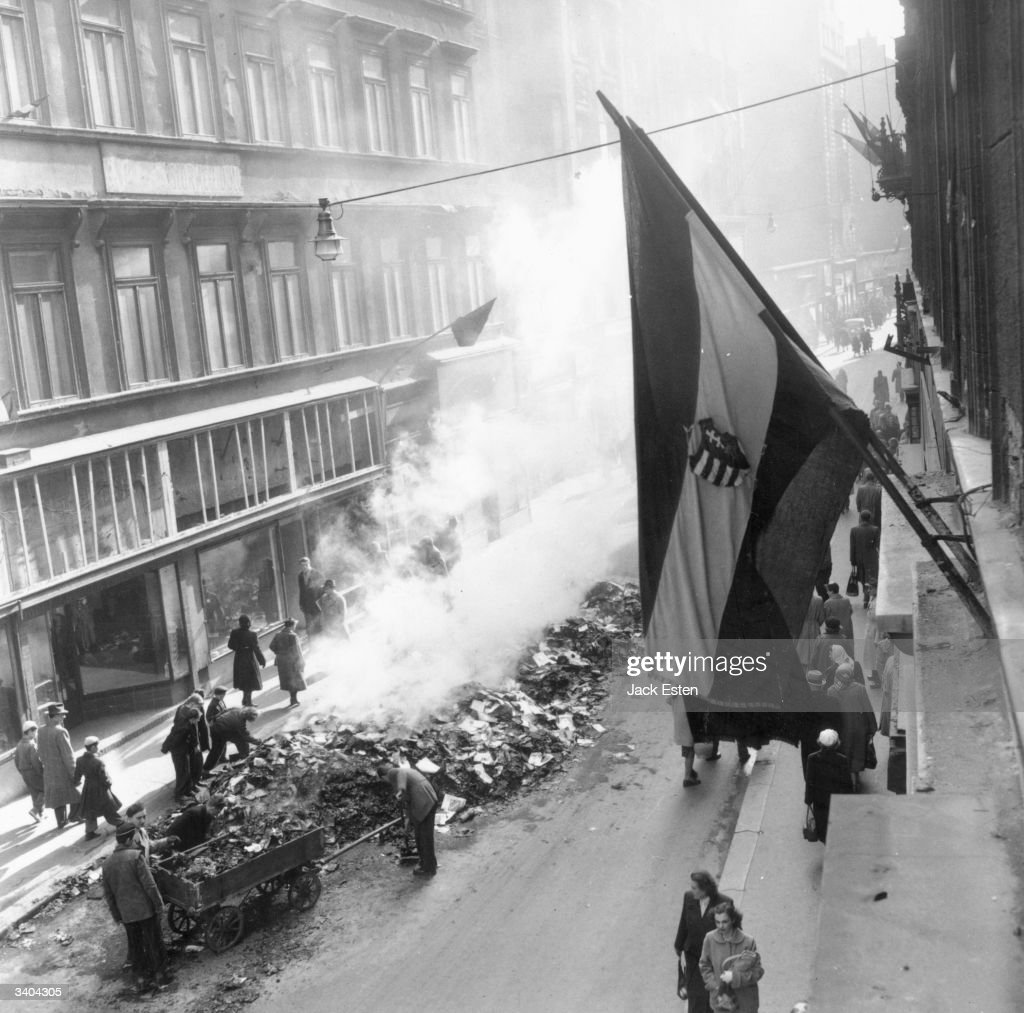 A flag flies over the street as Hungarian citizens clear the debris following the invasion of Russian tanks to crush recent reforms. Original Publication: Picture Post - 8730 - Hungary's Last Battle For Freedom - pub. 1956
