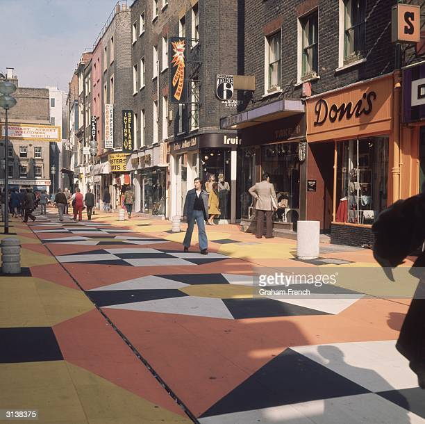London's fashionable Carnaby Street featuring new rubberised coloured paving tiles part of Westminster City Council's 60000 facelift for the...
