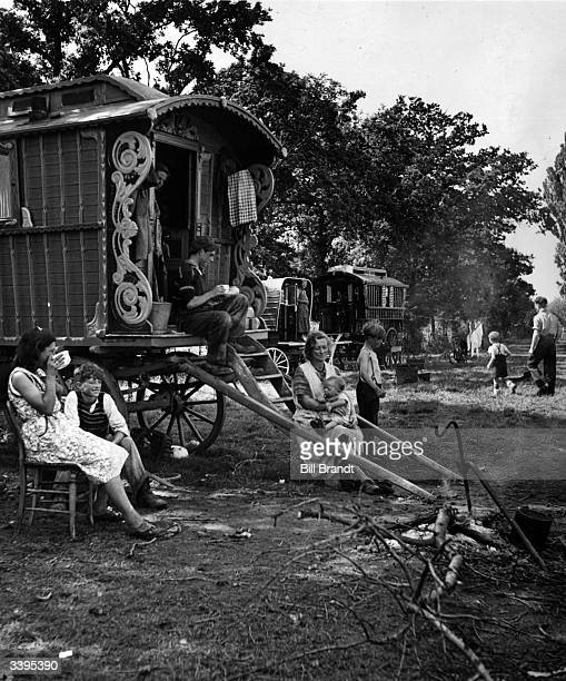 A family of gypsies sitting outside their caravan on an encampment at Brook Farm during the fruit picking season Original Publication Picture Post...