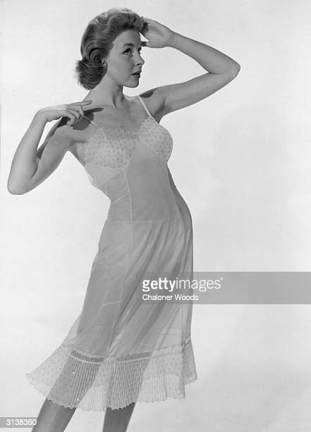 A Doris Day lookalike models a semitransparent petticoat or nightdress with a frilled hem