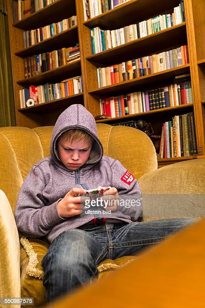 A 12yearold boy sitting in living room armchair and playing with his Gameboy The boy wearing a hooded sweater and looking focused on the display of...