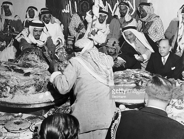 1/30/1947Seated at the head of the table during the banquet are King Ibn Saud whose retainer is using an ancient form of airconditioning and US...
