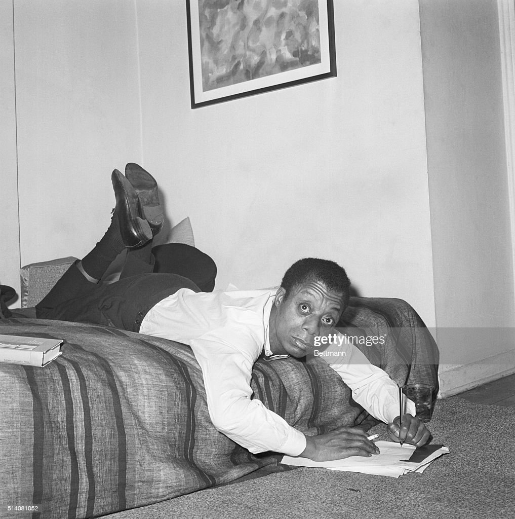 In a writing position that doesn't appear to be comfortable but really is, novelist James Baldwin sprawls across the bed in his New York apartment to jot some notes down. Baldwin, the author of 'Another Country' and other books, warns of the dangers of the 'fire' of racial conflict in his newest tome, 'The Fire Next Time.' The American Negro author deals with negro-white tensions in the United States and describes the anti-white Black Muslim movement and its origins in Negro bitterness and resentment over the white's treatment of them in both south and north.