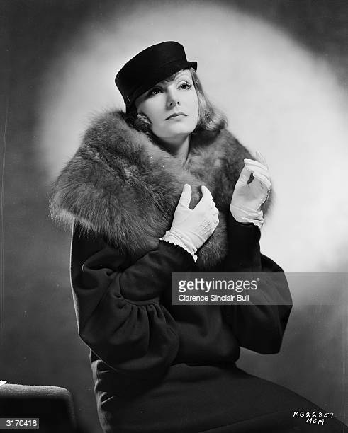 MGM star Greta Garbo wearing a coat with a fur collar and a small hat with a flat crown for her role as Grusinskaya in 'Grand Hotel' directed by...