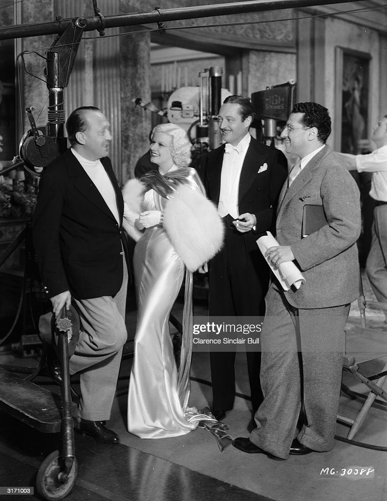 'Blonde Bombshell' Jean Harlow chats to British film director Edmund Goulding (left), who is visiting the set of the MGM film 'Dinner at Eight'. Actor Edmund Lowe and the film's director, George Cukor (right), look on. Costumes by Adrian.