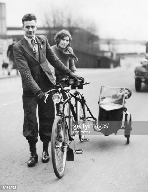 A young mother and father in South Wales take their baby for a ride in their tandem bicycle's sidecar