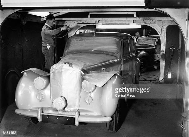 A man at work in a spray booth in the paint shop at the Rolls Royce factory in Crewe