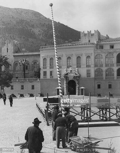 Workmen erecting a colourful flagstaff in the Place du Palais in front of the Palace of Monaco as part of the decorations being put in place for the...