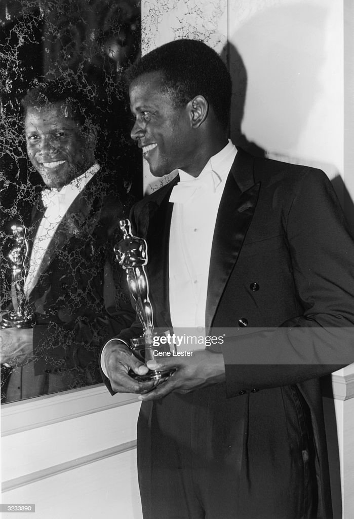 American actor Sidney Poitier looks into a mirror and smiles while holding his Best Actor Oscar for director Ralph Nelson's film, 'Lilies of the Field,' backstage at the Academy Awards, Santa Monica, California.
