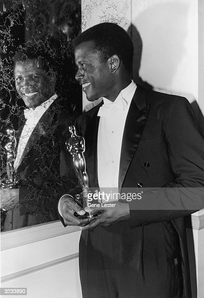 EXCLUSIVE American actor Sidney Poitier looks into a mirror and smiles while holding his Best Actor Oscar for director Ralph Nelson's film 'Lilies of...