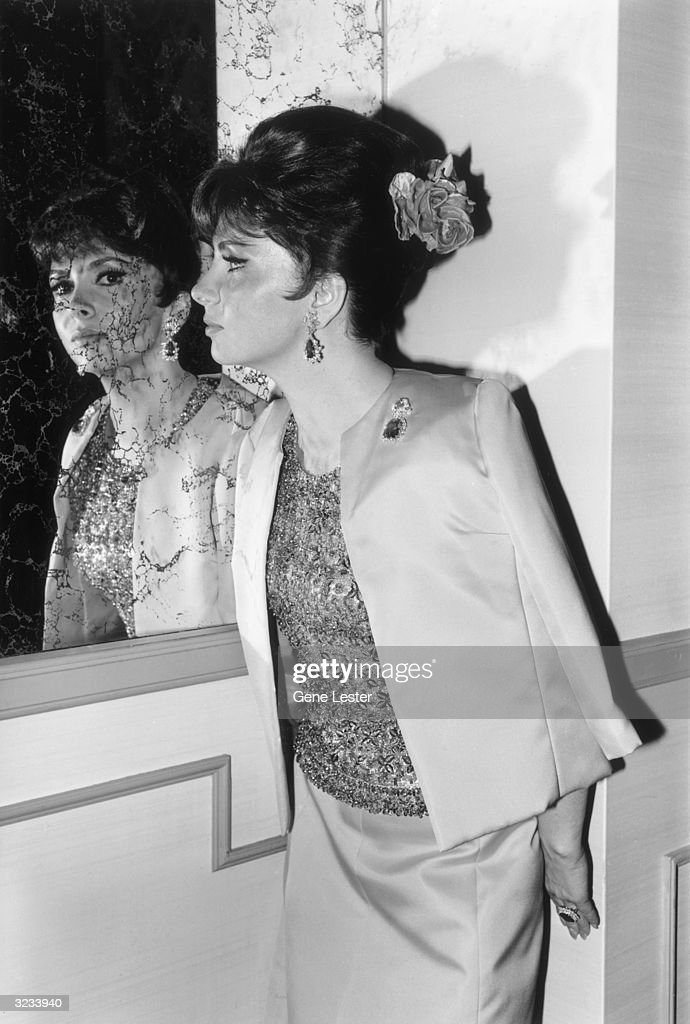 Italian actor Gina Lollobrigida faces a mirror while posing backstage at the Academy Awards, Santa Monica, California, April 13, 1964. She wears a sequined and beaded top with a silk jacket and matching skirt.