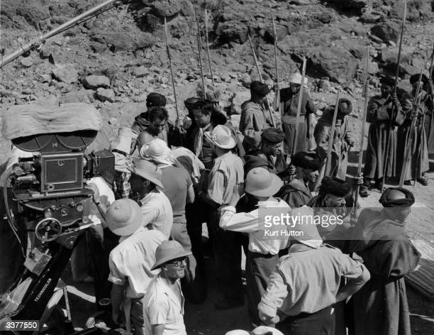 Crew members gather round actor Tyrone Power who has been bruised by enthusiastic spearcarrying extras during shooting of the 20th Century Fox film...