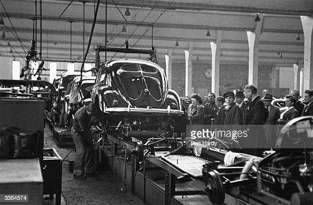 Workers at the chassis stage on the VW Beetle production line at the Volkswagen factory at Wolfsburg Germany Original Publication Picture Post 4854...