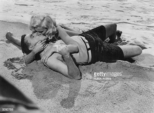 Dolores Rosedale and Tom Ewell embrace on a beach in a scene from Billy Wilder's romantic comedy 'The Seven Year Itch' The scene is a parody of the...