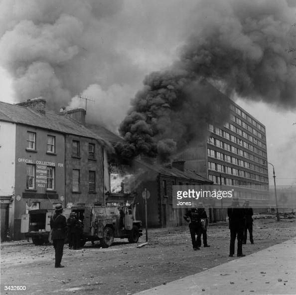 Heavy black smoke billows from a building after a bomb attack in the Bogside area of Belfast Firemen are in attendance