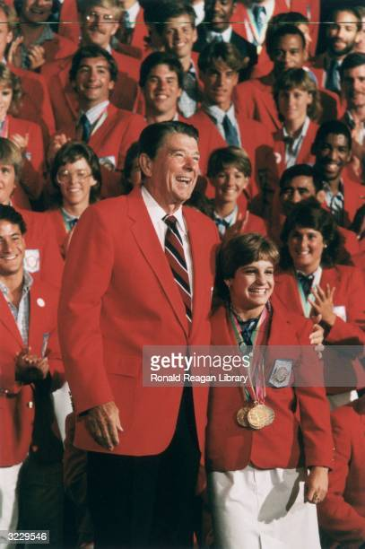 US President Ronald Reagan stands with his arm around the shoulders of US Olympic champion gymnast Mary Lou Retton as other Olympic athletes clap...