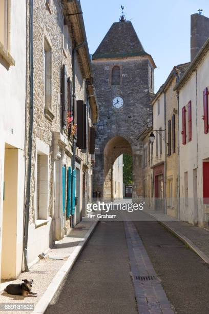 13th Century medieval gateway clock tower dog in empty street in ancient bastide fortified town on September 20 2015 in Duras in Aquitaine France