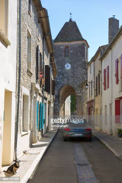 13th Century medieval gateway clock tower VW Beetle car and dog in ancient bastide town on September 20 2015 in Duras in Aquitaine France
