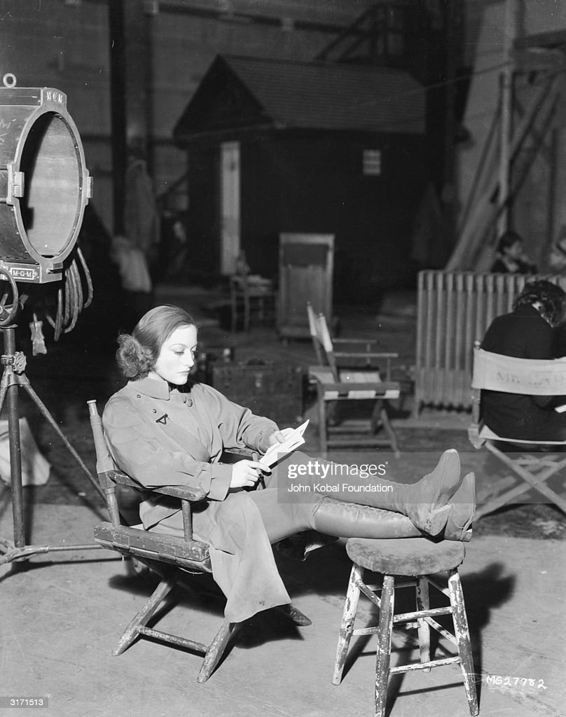 American actress Joan Crawford (1904 - 1977) reading on the set of her latest film 'Today We Live'.