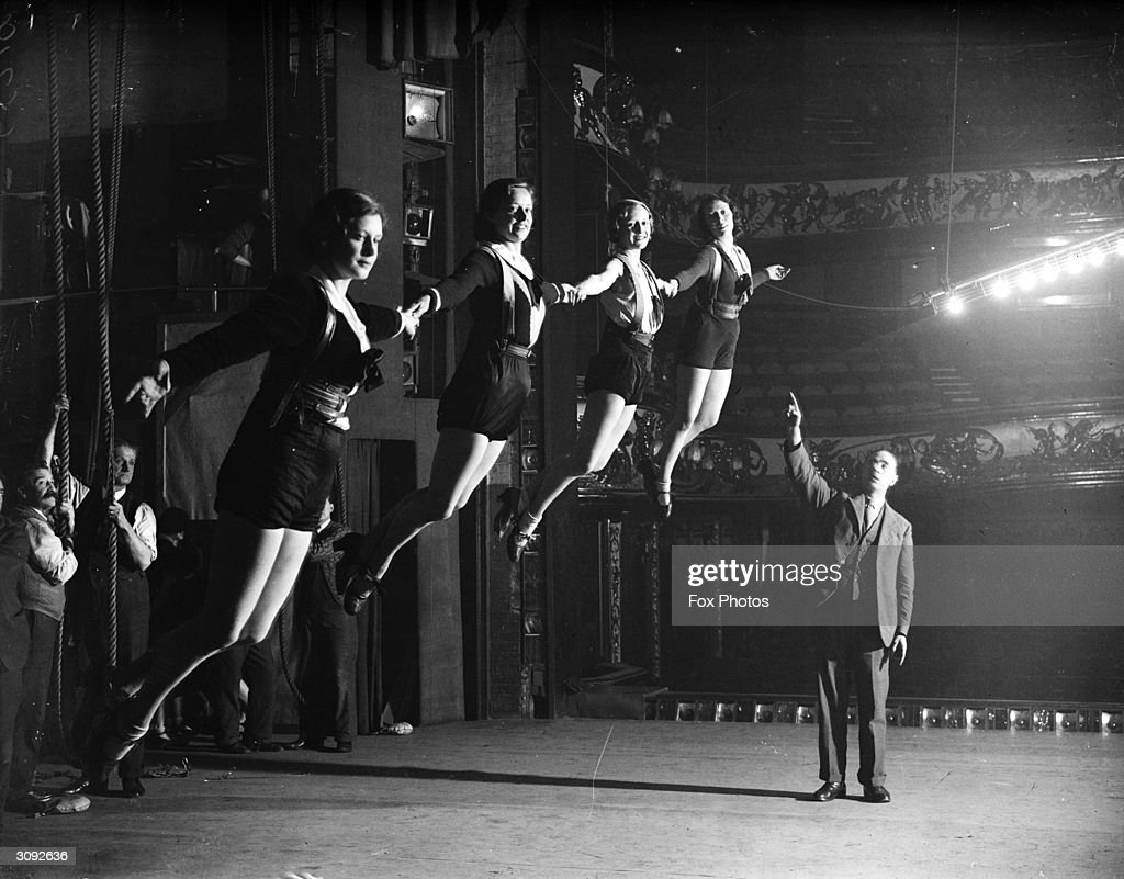 Four of Daly's chorus girls are hoisted aloft on 'invisible' wires during a rehearsal for the pantomine 'Mother Goose'.